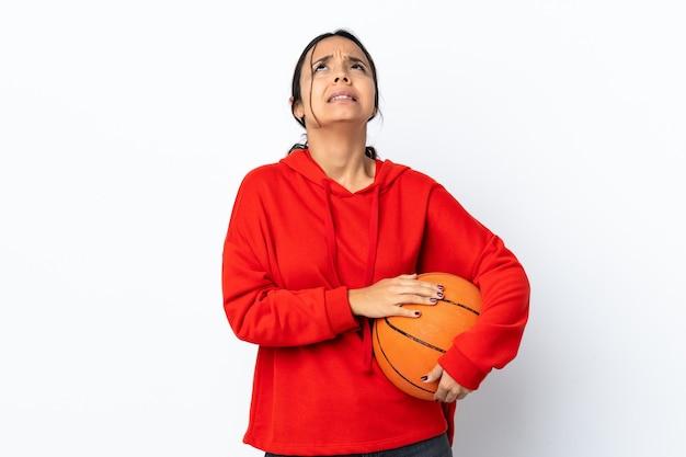Junge frau, die basketball über isolierte weiße wand spielt, hält palme zusammen. person fragt nach etwas