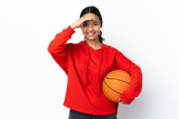 Junge frau, die basketball über isoliertem weißem gruß mit hand mit glücklichem ausdruck spielt