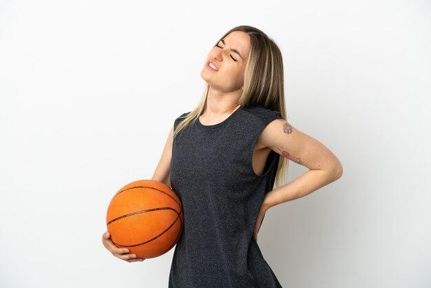 Junge frau, die basketball über isolierter weißer wand spielt, die unter rückenschmerzen leidet, weil sie sich angestrengt hat?