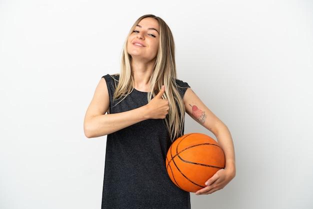 Junge frau, die basketball über isolierter weißer wand spielt und eine geste mit dem daumen nach oben gibt
