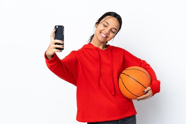Junge frau, die basketball über lokalisiertem weißem hintergrund spielt, der ein selfie macht