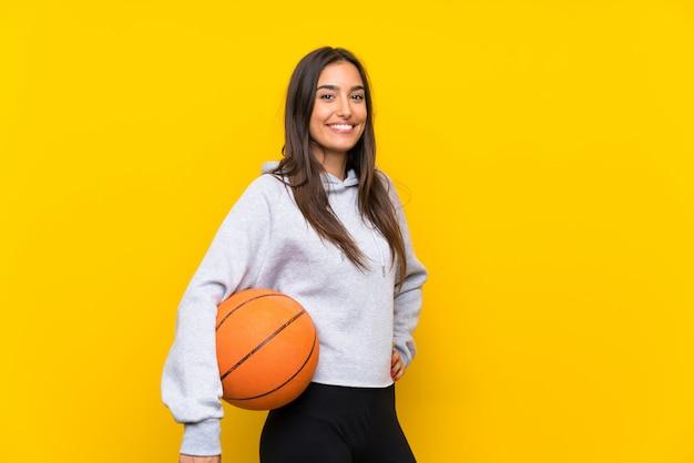 Junge frau, die basketball über lokalisierter gelber wand spielt