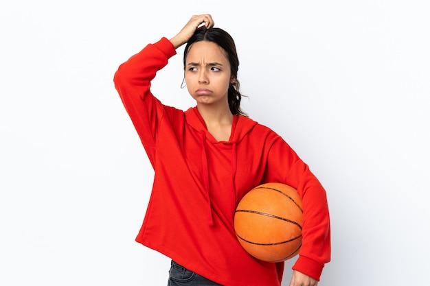 Junge frau, die basketball über weißer wand spielt, die zweifel beim kratzen des kopfes hat