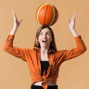 Junge frau, die basketballball spielt
