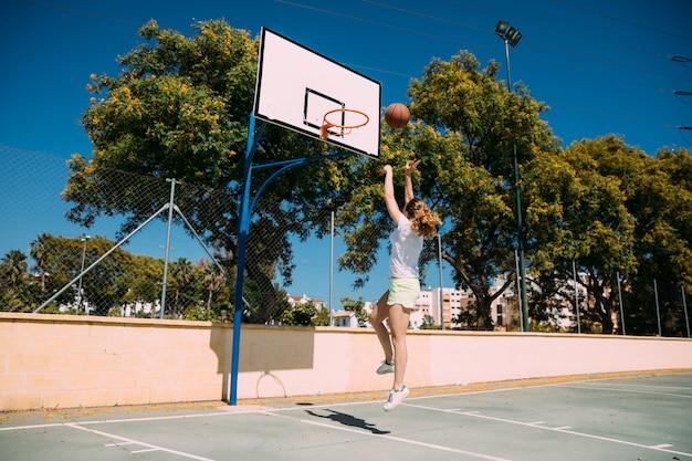 Junge frau, die basketballsprungschuß bildet