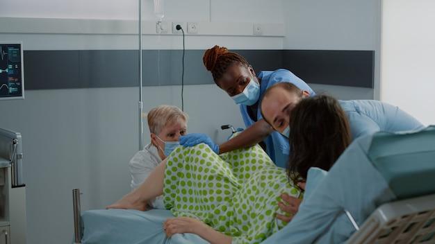 Junge frau, die bei der geburt eines kindes in der krankenstation drückt
