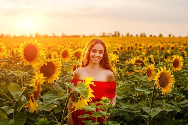 Junge frau, die bei sonnenuntergang in einem sonnenblumenfeld lächelt, ein süßes mädchen von kaukasischem aussehen in einem roten ...