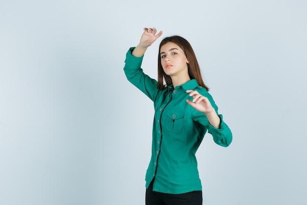 Junge frau, die beim erhöhen der hände im grünen hemd aufwirft und zuversichtlich schaut. vorderansicht.