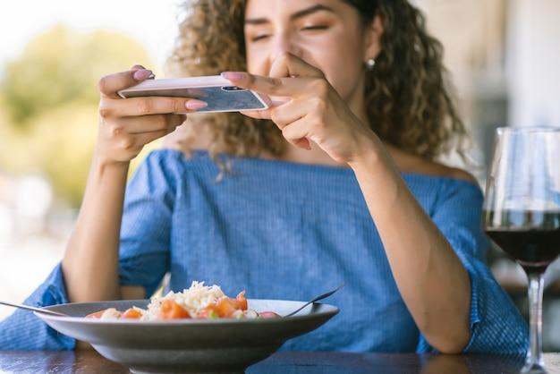 Junge frau, die beim mittagessen in einem restaurant ein foto zum essen macht.