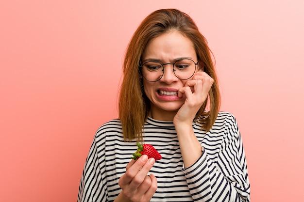 Junge frau, die beißende fingernägel einer erdbeere, nervös und sehr besorgt hält.
