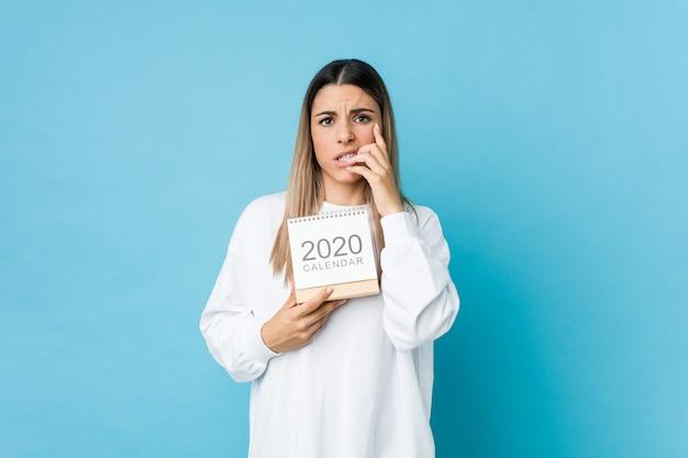 Junge frau, die beißende fingernägel eines kalenders 2020, nervös und sehr besorgt hält
