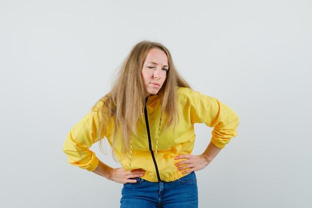 Junge frau, die biegt, während hände auf taille hält und in gelber bomberjacke und blauer jeans zwinkert und charmant aussieht. vorderansicht.