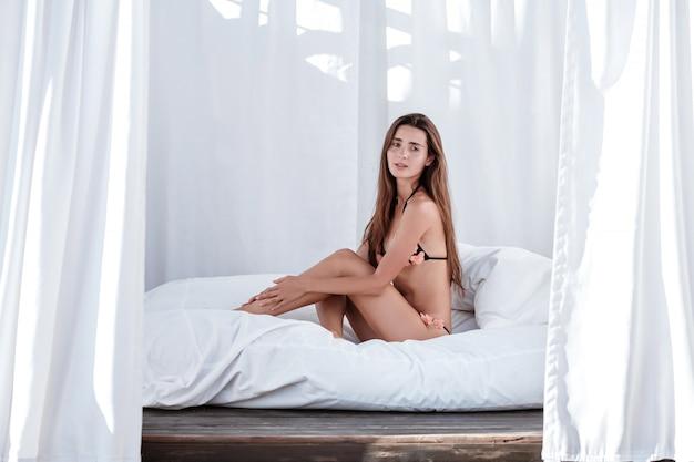 Junge frau, die bikini trägt, die ihre sommerferien genießt und sich auf dem strandbett entspannt