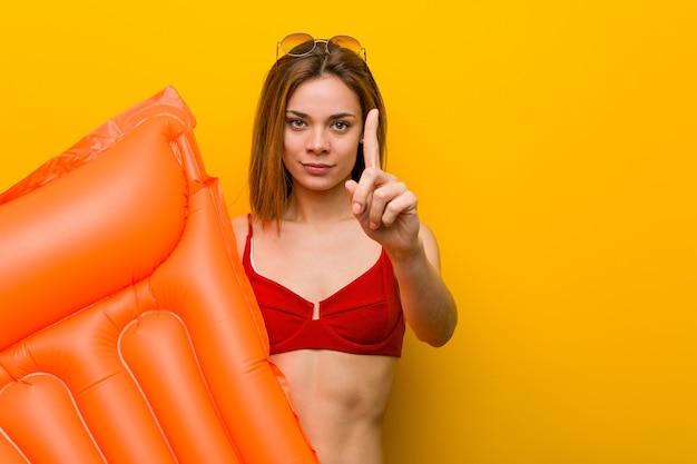 Junge frau, die bikini trägt und ein luftmatratzebett hält, das nummer eins mit finger zeigt.