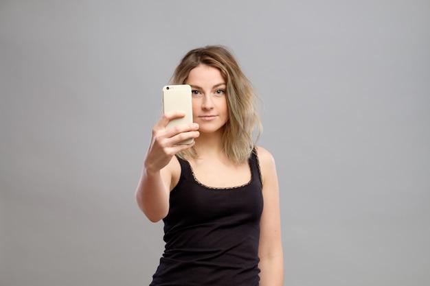 Junge frau, die bilder durch ihr telefon macht
