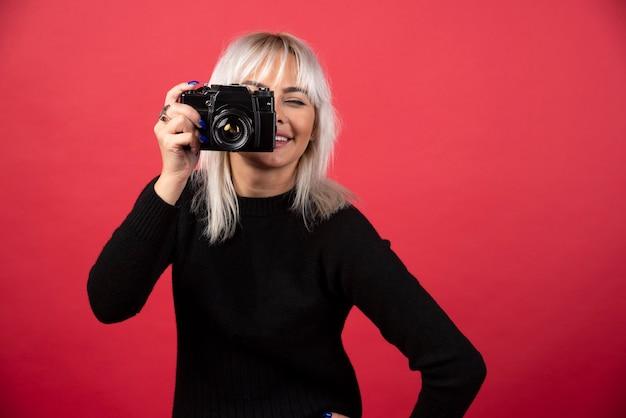 Junge frau, die bilder mit einer kamera auf einem roten hintergrund nimmt. hochwertiges foto