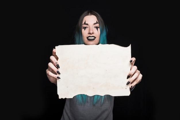 Junge frau, die blatt papier im studio hält