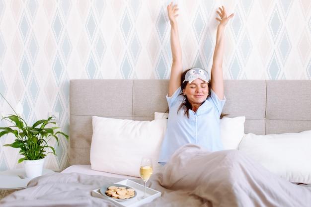 Junge frau, die blaue pyjanas und schlafmaske trägt, die glücklich nach einem guten schlaf mit ihren händen oben aufwachen.