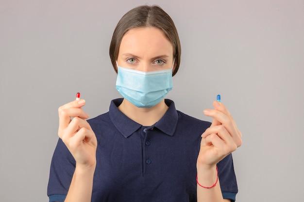 Junge frau, die blaues poloshirt in der medizinischen schutzmaske hält, die pillen in der hand betrachtet kamera mit ernstem gesicht auf hellgrauem hintergrund hält