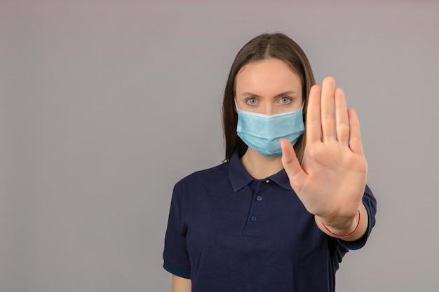 Junge frau, die blaues poloshirt in der medizinischen schutzmaske trägt, die handstoppgeste mit ernstem gesicht lokalisiert auf hellgrauem hintergrund mit kopienraum zeigt