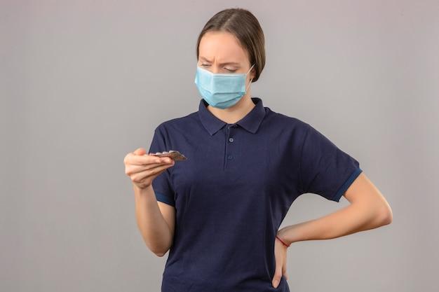 Junge frau, die blaues poloshirt in der schützenden medizinischen maske hält, die blisterpillen in der hand betrachtet, die pillen mit ernstem gesicht stehen auf hellgrauem hintergrund stehen