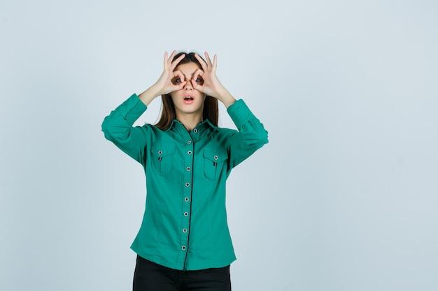 Junge frau, die brillengeste im grünen hemd zeigt und verwundert schaut. vorderansicht.