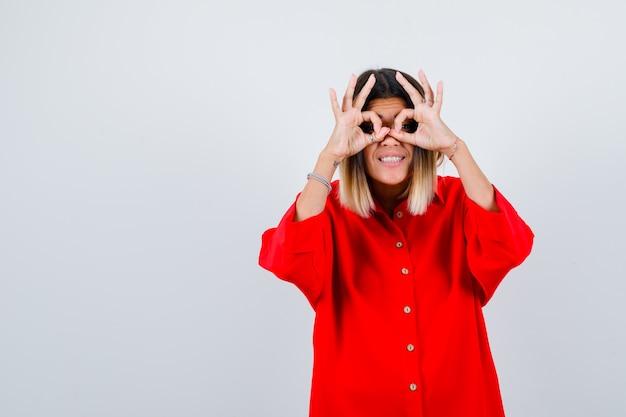 Junge frau, die brillengeste im roten übergroßen hemd zeigt und glücklich schaut. vorderansicht.