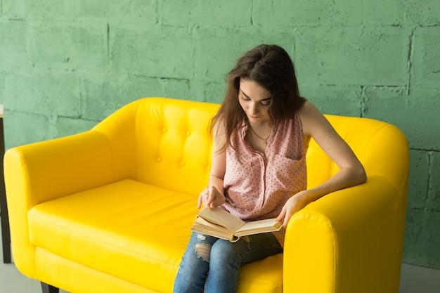 Junge frau, die buch auf gelbem sofa liest