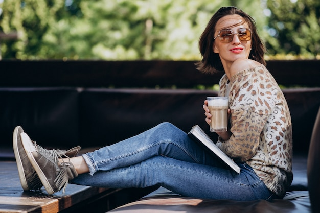 Junge frau, die buch liest und kaffee trinkt