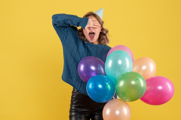 Junge frau, die bunte luftballons auf gelb hält