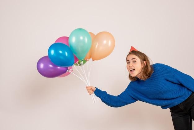 Junge frau, die bunte luftballons auf weiß hält