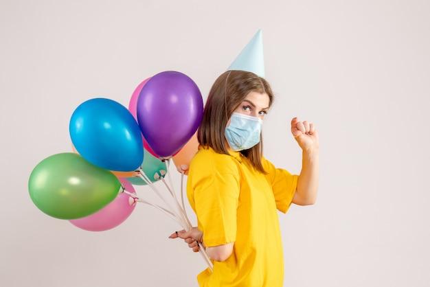 Junge frau, die bunte luftballons hinter ihrem rücken in der maske auf weiß versteckt