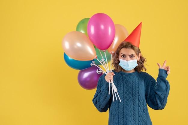 Junge frau, die bunte luftballons in der maske auf gelb hält