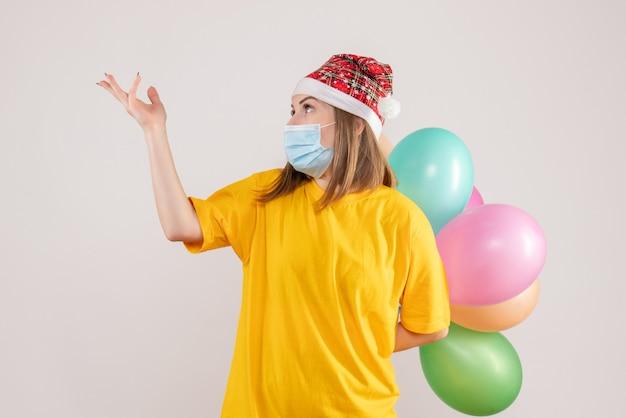 Junge frau, die bunte luftballons in der maske auf weiß hält