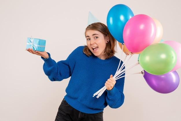 Junge frau, die bunte luftballons und wenig geschenk auf weiß hält