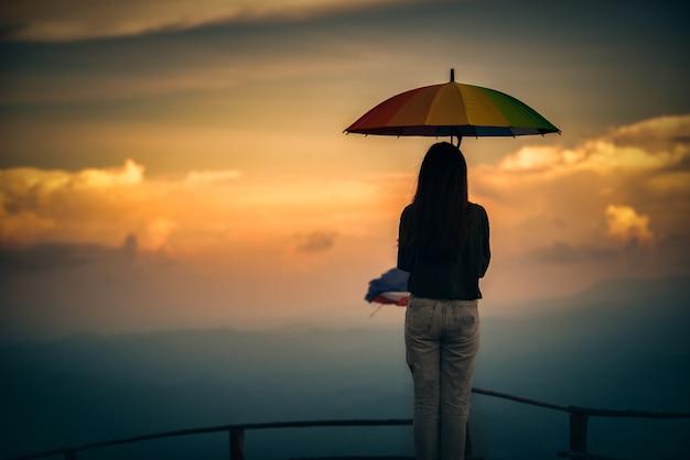 Junge frau, die bunten regenschirm schaut regen in den bergen hält