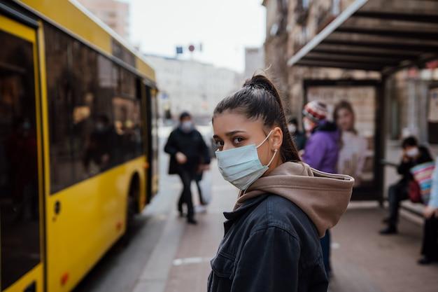 Junge frau, die chirurgische maske draußen an der bushaltestelle in der straße trägt