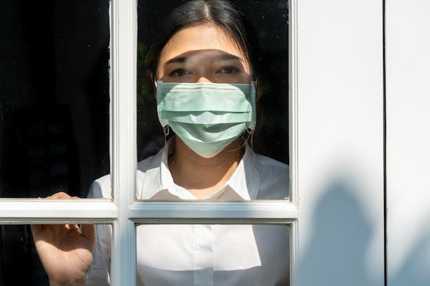 Junge frau, die chirurgische maske trägt, die in ihrem haus bleibt und aus der vordertür besorgt betrachtet