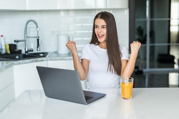 Junge frau, die computer-laptop an der küche verwendet, die stolz schreit und sieg und erfolg sehr aufgeregt feiert