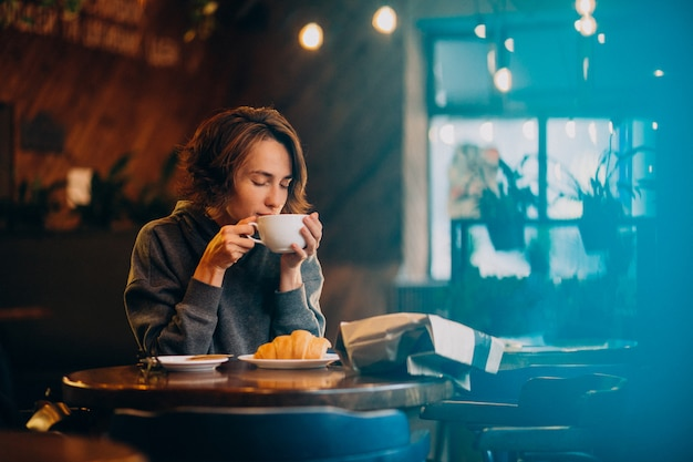 Junge frau, die croissants an einem café isst