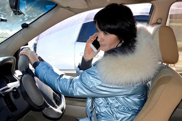Junge frau, die das auto fährt und am telefon spricht