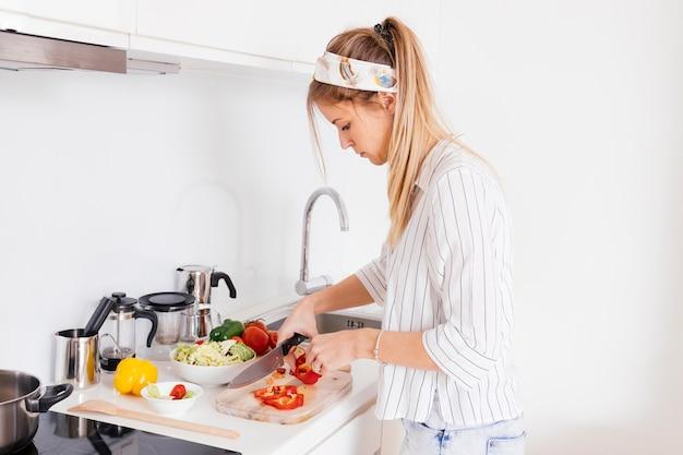 Junge frau, die das bellpepper mit messer auf küchenarbeitsplatte schneidet