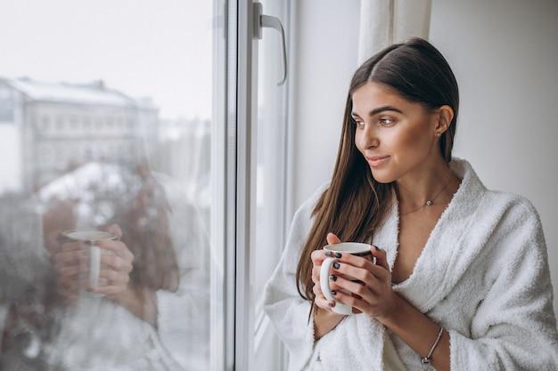 Junge frau, die das fenster trinkt heißen kaffee bereitsteht