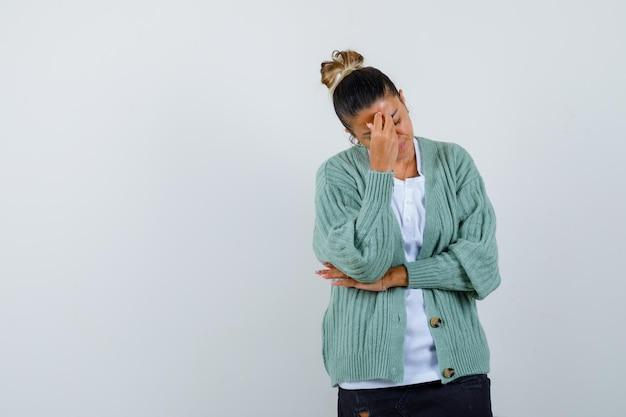 Junge frau, die das gesicht mit der hand bedeckt, während sie die hand am ellbogen in weißem hemd und mintgrüner strickjacke hält und gehetzt aussieht