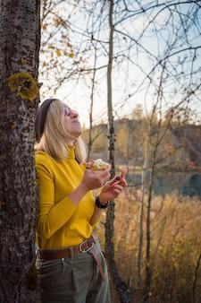 Junge frau, die das leben in der natur genießt, isst einen apfel und lacht.