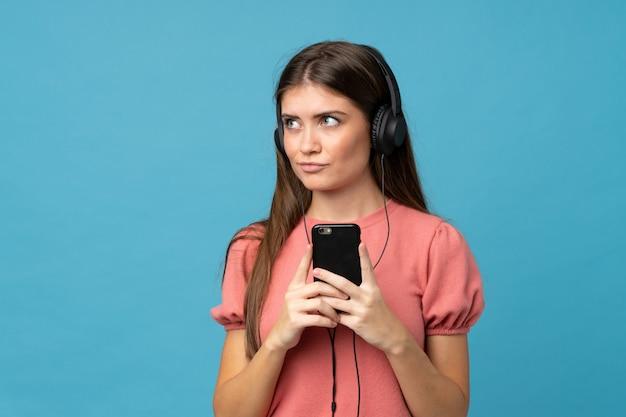 Junge frau, die das mobile mit kopfhörern und dem denken verwendet