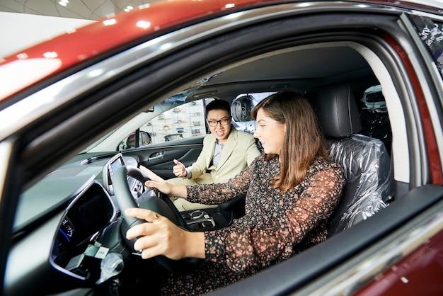Junge frau, die das neue auto zusammen mit verkäufer testet, während sie im salon des autos sitzen