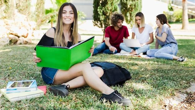 Junge frau, die das sitzen auf gras nahe universität studiert
