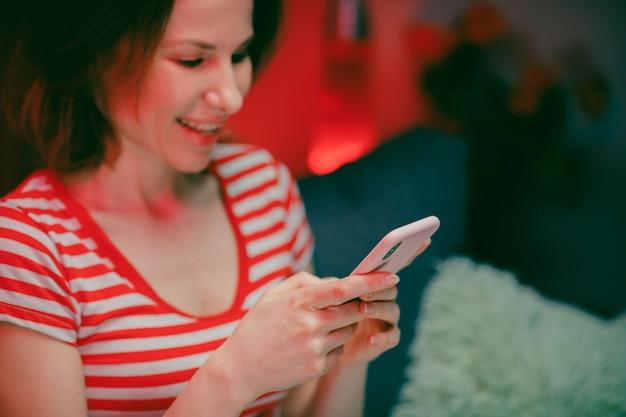 Junge frau, die das smartphone hält, das handy-bildschirm mit mobilen apps zum einkaufen betrachtet