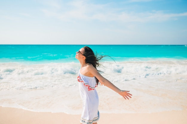 Junge frau, die das sonnenbaden durch perfektes türkisfarbenes meer genießt